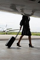Side profile of a cabin crew pulling her luggage near a private airplane