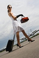 Side profile of a young woman pulling her luggage