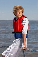 Teenage boy in lifejacket on boat (thumbnail)