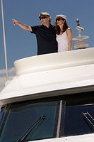 Mature adult couple on boat and pointing into distance