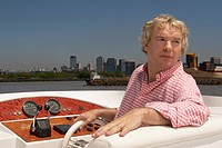 Mature adult man steering boat