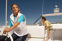 Young couple on boat with woman steering (thumbnail)