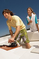 Young happy couple on boat with man steering
