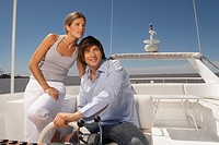 Young couple steering boat