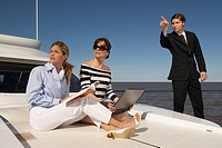 Businessman pointing into distance on boat and women looking