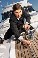 Upset businessman pulling chain on boat