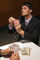 Businessmen playing cards for money