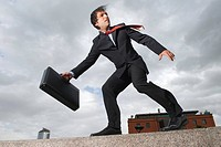 Businessman with briefcase standing on windy ledge