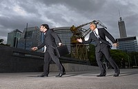 Businessmen walking on street in the wind