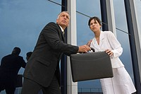 Concerned businesspeople exchanging briefcase outdoors
