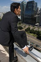 Suicidal businessman contemplating jumping off roof