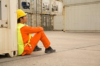 Side profile of a male dock worker sitting at a commercial dock leaning against a cargo container