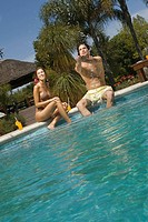 Young couple sitting at the poolside