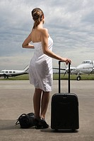 Rear view of a young woman standing at an airport and holding her luggage