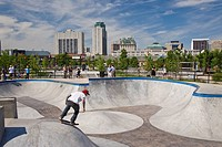 View of The Plaza urban landscape designed and built for skateboarders, BMX cyclists and inline skaters at The Forks with downtown Winnipeg in backgro...