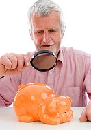 retiree watching piggy bank under loupe