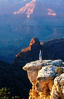 A woman standing on a cliff in Grand Canyon, Arizona, USA