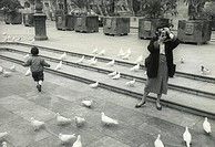 A photographer, a little boy and pigeons