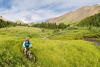 Mountain biker rides down from Windy Pass, Southern Chilcotin Mountains, British Columbia, Canada.