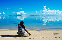 Cook Islands, South Pacific, local woman sits on tropical beach, Rarotonga