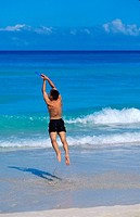 Mexico, Yucatan Peninsula, Carribean resort at Cancun, man catches frisbee