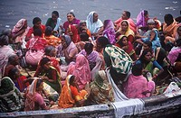 India, Varanasi, Hindu pilgrims crowd onto river boat on the Ganges