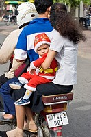 A family on a motor bike in Cambodia at Christmastime.