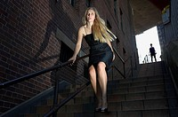 Young woman rushing down urban stairway with a sense of fear as a man follows her