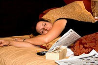 Woman age 38 resting on bed with newspaper, book and remote  St Paul Minnesota USA