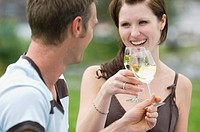 Young couple clinking glasses of white wine out of doors