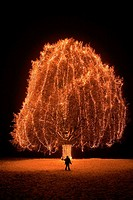 Little boy standing in front of big tree with christmas lights at night time, snow, Switzerland