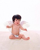 Portrait of baby girl in angel wings, smiling, front view