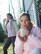 Two women drinking coffee in lawn