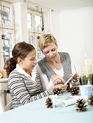 Woman helping teenage girl to make christmas ornaments
