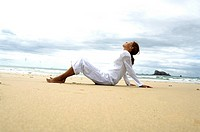 Side profile of woman meditating on beach