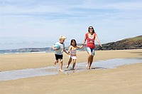 Woman running with her children on beach