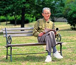 Senior adult man sitting on a bench, Front View