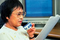 Senior adult woman reading documents with a cup in hand, Side View