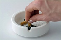 Females Hand Stubbing Out A Cigarette In An Ashtray