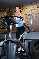Adult Caucasian female on elliptical machine at gym