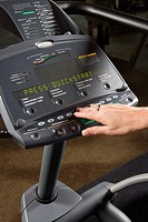 Adult Caucasian female setting up elliptical machine at gym