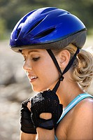 Caucasian mid_adult woman putting on bicycle helmet