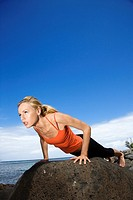Caucasian young adult woman doing push up on rock