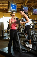 Adult Caucasian female on elliptical machine at gym with trainer