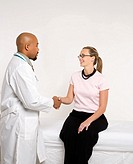 Mid_adult African_American doctor and Caucasian mid_adult female patient shaking hands in doctor's office