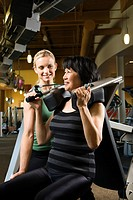Adult Caucasian female trainer helping Asian mature adult female on exercise machine