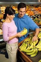 Caucasian mid_adult couple grocery shopping for bananas