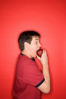 Portrait of Caucasian teen boy biting an apple standing against red background