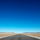 Strip of highway stretching towards horizon under clear blue sky