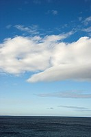 Blue sky with fluffy white clouds over ocean horizon (thumbnail)